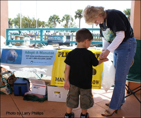 SMC Volunteer Kathleen Phillips assists a young manatee lover with a stamp.