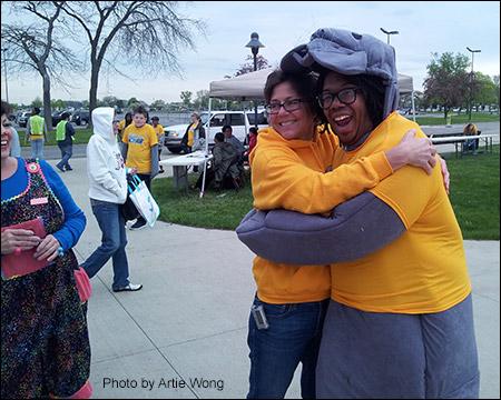 Race Director Lesley Argiri gives a big hug to the 5K manatee mascot.