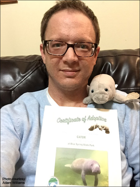 Adam Williams holds his manatee adoption certificate.