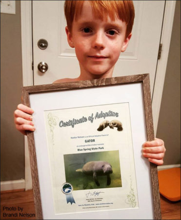 Hunter with his adoption certificate for the manatee named Gator.