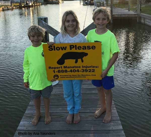 Children with manatee dock sign
