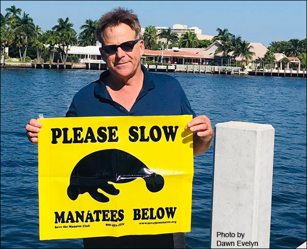 "Actor Kin Shriner with ""Please Slow"" manatee banner."