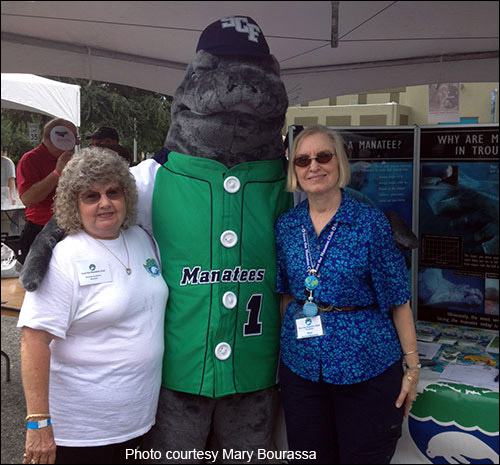 Save the Manatee Club volunteers Mary Bourassa (at right) and Norma Khueler at an event with the State College of Florida manatee mascot.