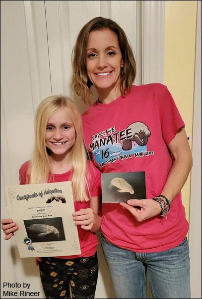 Heather Koch and daughter Alix hold manatee adoptions.